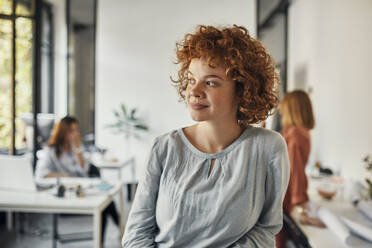 Portrait of a redheaded businesswoman in office looking sideways - ZEDF02819