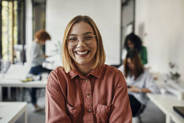 Portrait of a happy businesswoman in office with colleagues in background - ZEDF02825