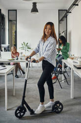 Portrait of a businesswoman with kick scooter in office - ZEDF02828