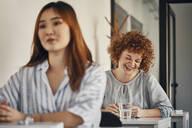 Happy businesswoman sitting at desk in a workshop - ZEDF02843