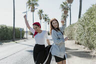Two female friends dancing on the street - ERRF02197