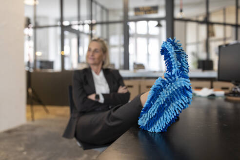 Mature businesswoman with feet on desk wearing cleansing slippers in office - GUSF02699