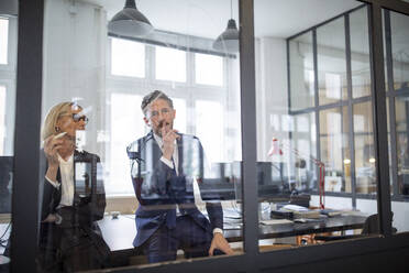 Businessman and businesswoman looking at drawing on glass pane in office - GUSF02705