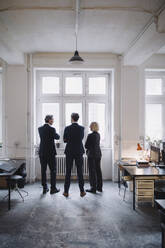 Business people standing at the window in office - GUSF02717