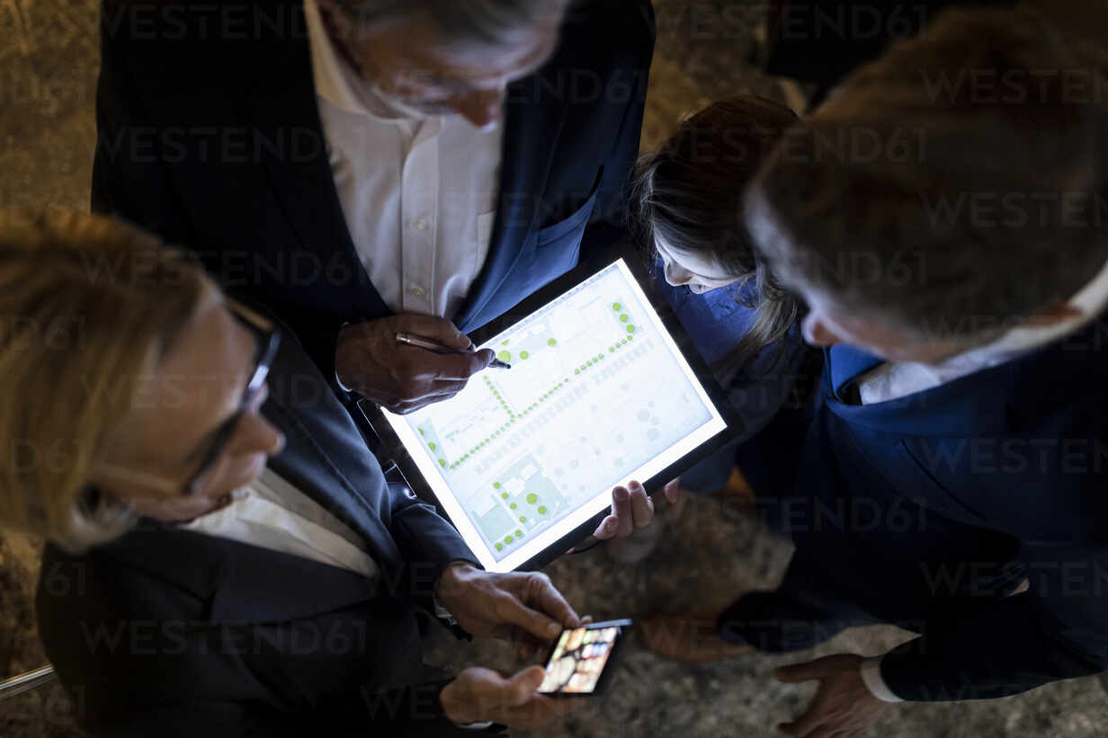 Top view of business people and girl looking at shining construction plan on tablet in office - GUSF02723 - Gustafsson/Westend61