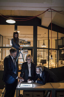 Business people discussing at shining tablet in office with girl on ladder standing besides - GUSF02732