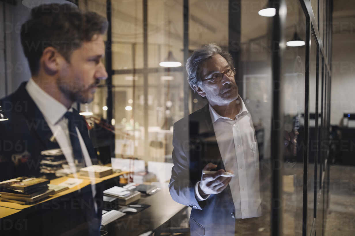 Two businessmen working on drawing on glass pane in office - GUSF02741 - Gustafsson/Westend61