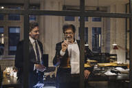 Two businessmen working on drawing on glass pane in office - GUSF02747