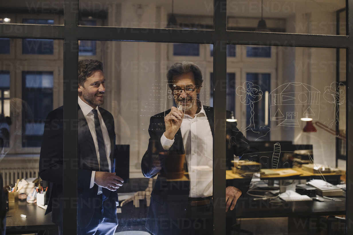 Two businessmen working on drawing on glass pane in office - GUSF02747 - Gustafsson/Westend61