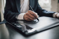 Close-up of businessman using graphics tablet at desk in office - GUSF02768