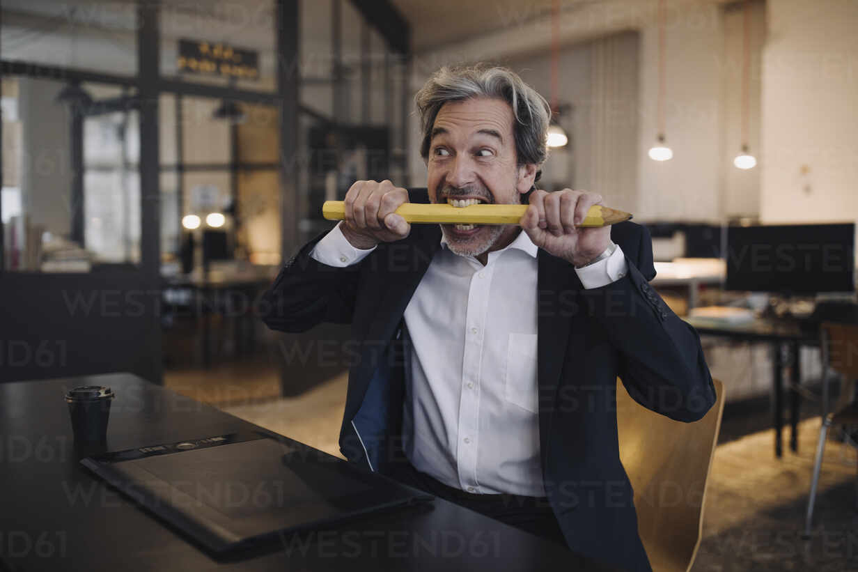 Angry senior businessman with giant pencil at desk in office - GUSF02774 - Gustafsson/Westend61
