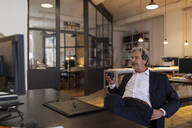 Relaxed senior businessman sitting at desk in office - GUSF02777