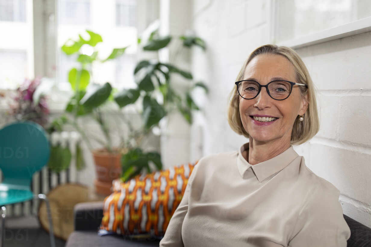 Portrait of smiling mature businesswoman on couch in office lounge - GUSF02783 - Gustafsson/Westend61