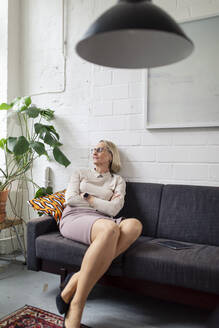 Mature businesswoman sitting on couch in office lounge with closed eyes - GUSF02786