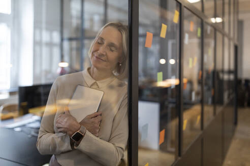 Mature businesswoman with closed eyes leaning against glass pane in office - GUSF02792