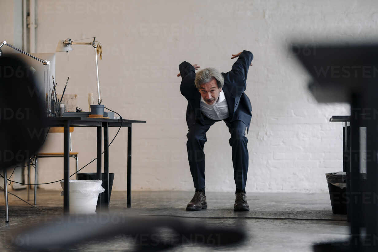 Senior businessman doing gymnastics in office - GUSF02807 - Gustafsson/Westend61
