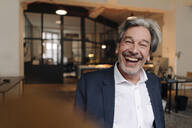 Portait of laughing senior businessman in office - GUSF02816