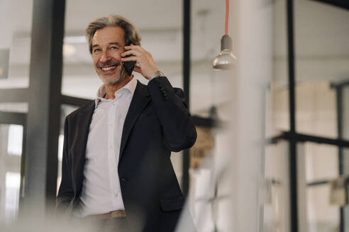 Smiling senior businessman on the phone in office - GUSF02822