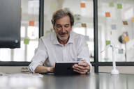 Senior businessman using tablet in conference room in office - GUSF02852