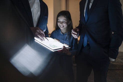 Business people and happy girl looking at shining construction plan on tablet in office - GUSF02882