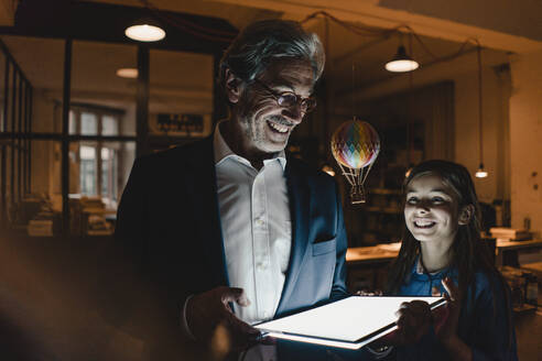 Happy senior buisinessman and girl with hot-air balloon and shining tablet in office - GUSF02903