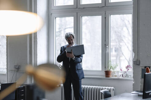 Senior businessman using laptop at the window in office - GUSF02918