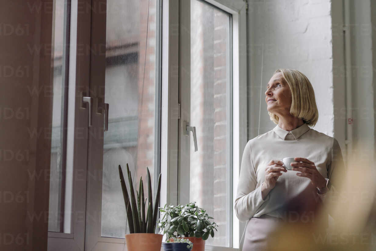 Mature businesswoman having a coffee break at the window in office - GUSF02927 - Gustafsson/Westend61