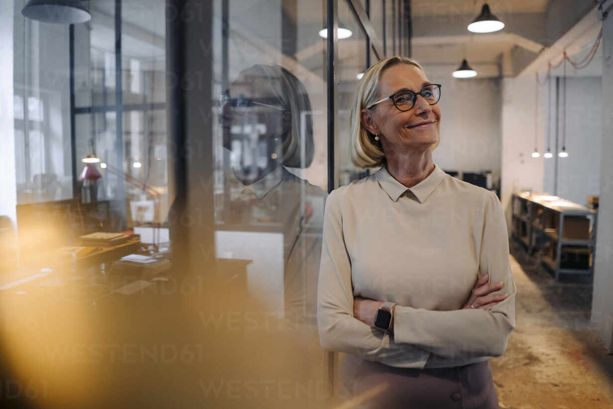 Portrait of smiling mature businesswoman leaning against glass pane in office - GUSF02936 - Gustafsson/Westend61
