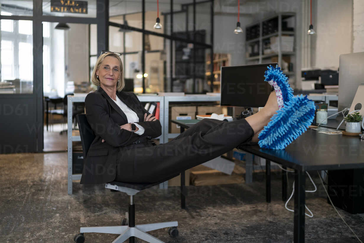 Mature businesswoman with feet on desk wearing cleansing slippers in office - GUSF02939 - Gustafsson/Westend61