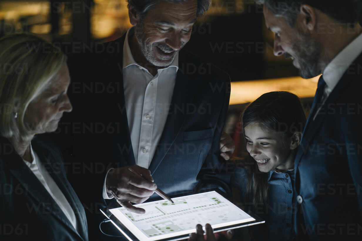 Business people and girl looking at shining tablet in office - GUSF02945 - Gustafsson/Westend61