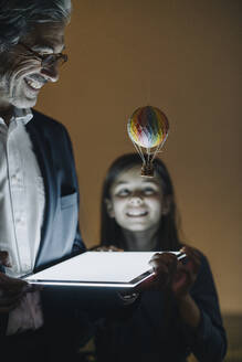 Happy senior buisinessman and girl with hot-air balloon and shining tablet in office - GUSF02948