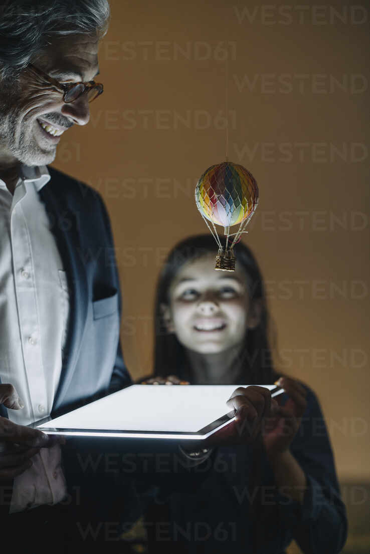 Happy senior buisinessman and girl with hot-air balloon and shining tablet in office - GUSF02948 - Gustafsson/Westend61