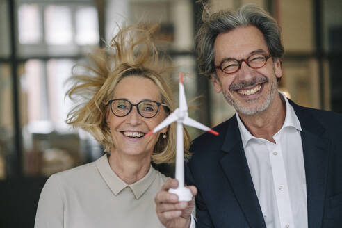 Portrait of happy businessman and businesswoman holding wind turbine model in office - GUSF02951