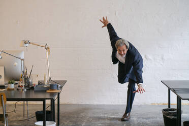 Senior businessman doing gymnastics in office - GUSF02954