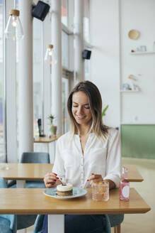 Young woman enjoying her cake - MOMF00824