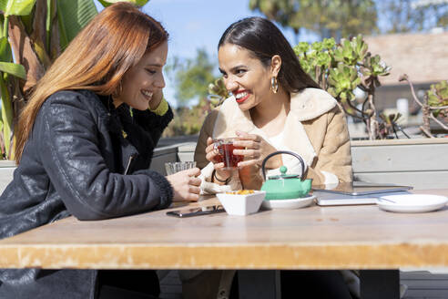 Two female friends drinking tea outdoors at a coffee shop - ERRF02200