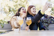 Two female friends taking a selfie outdoors at a coffee shop - ERRF02203