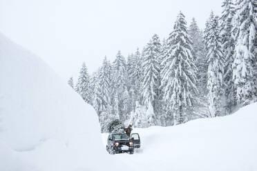 Austria, Salzburger Land, Lammertal, Man attaching Christmas tree to car roof on snowy road - HHF05579