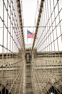 USA, New York, New York City, Cables of Brooklyn Bridge with American flag standing on top - CJMF00177