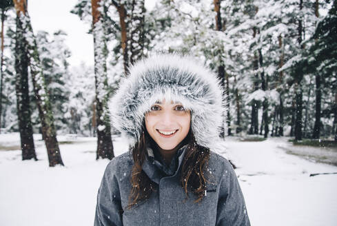 Portrait of happy young woman in winter forest - OCMF00929