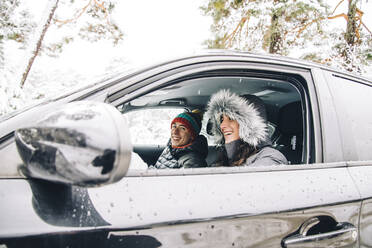 Happy young couple sitting in a car in winter forest having fun - OCMF00932