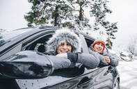 Portrait of happy young couple sitting in a car in winter forest having fun - OCMF00935