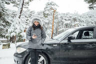 Portrait of smiling young woman leaning at parked car in winter forest looking at cell phone - OCMF00941