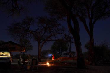 Woman on a campsite at night at a campfire, Khwai, Botswana - VEGF00859