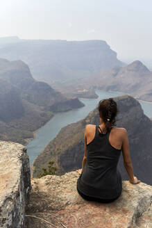 Woman on the top of a rock regarding the breathtaking landscape. Blyde River Canyon, South Africa. - VEGF00874