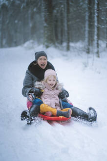 Portrait of mature woman sledging together with her daughter - PSIF00336
