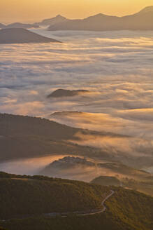 Italy, Aerial view of thick morning fog shrouding forested valley inApennineMountains - LOMF00934