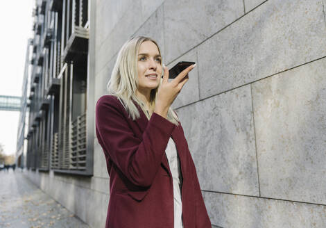 Blond businesswoman using smartphone in the city - AHSF01358