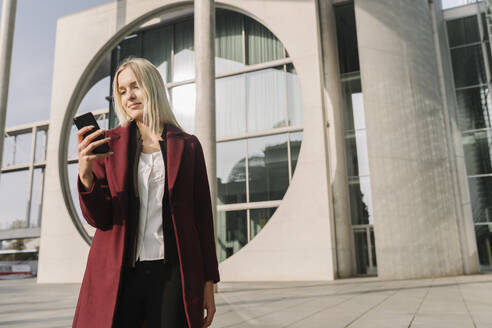 Germany, Berlin, Businesswoman using smartphone in the background of modern buildings - AHSF01361