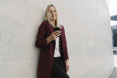 Blond businesswoman using smartphone and leaning on a wall - AHSF01364